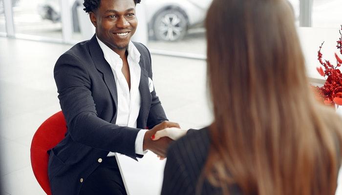 Foto mostra duas pessoas dando um aperto de mãos, como quem aplica técnicas de vendas