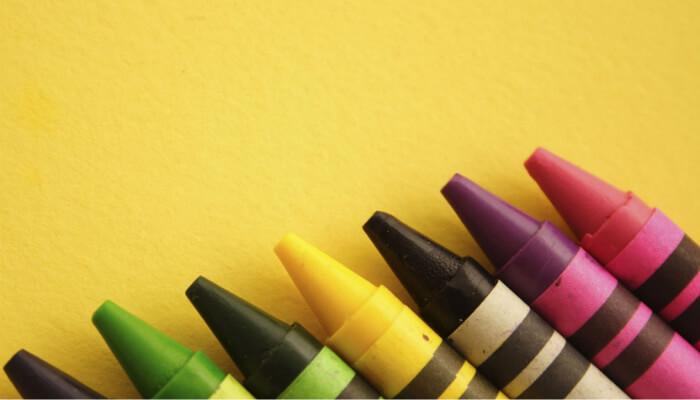 Imagem de coleção de giz de cera coloridos sobre fundo amarelo, representando curso de design para layout de loja virtual