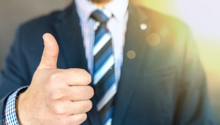 Homem de terno fazendo sinal de positivo com a mão, representando os likes que dão engajamento no Facebook