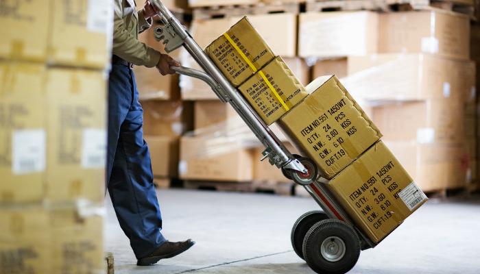 Foto que mostra dos ombros pra baixo de um homem empurrando um carrinho com caixas por um depósito, representando o estoque do e-commerce
