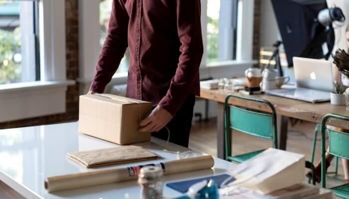 Homem embalando encomenda, representando o frete para loja virtual