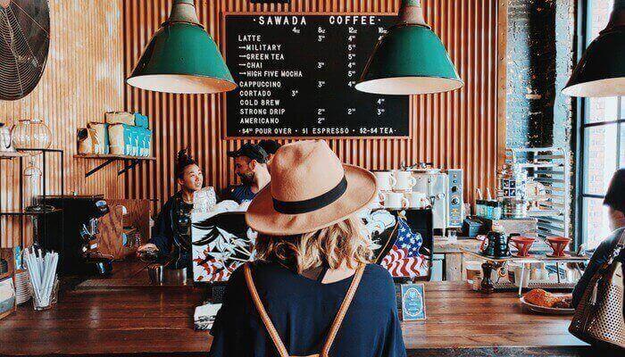Mulher de costas, em frente a balcão de atendimento de cafeteria
