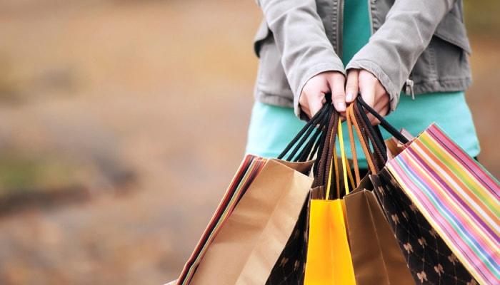 Mãos seguram sacolas de compras online de uma loja em acordo com a Lei do E-commerce
