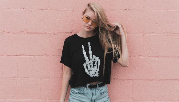 Modelo loira em frente a uma parede rosa olha para a câmera. Ela usa uma blusa preta com ilustração de ossos da mão fazendo símbolo de paz e amor, representando a loja de camisetas online