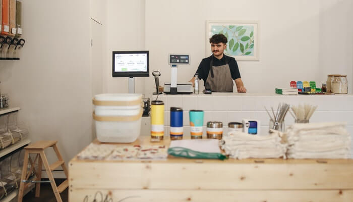 Foto de um homem atrás de um balcão em uma loja física, com computador para organizar pedidos também do ecommerce