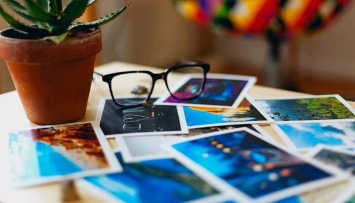 Mesa com fotos no estilo Polaroid espalhadas em cima, com par de óculos sobre elas, representando o marketing no Pinterest