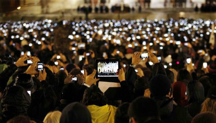 Imagem de multidão com tablets e celulares levantados, representando a possibilidade de usar a Nuvemshop mobile