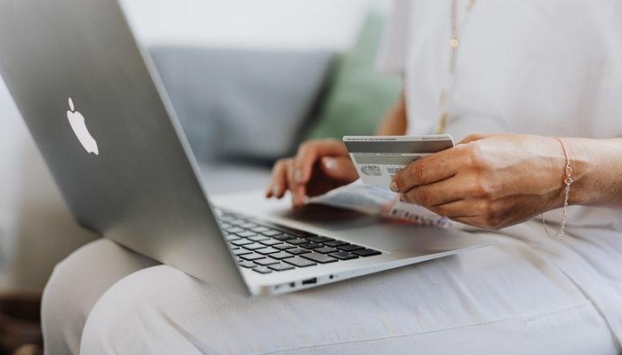 Imagem mostrando uma mulher fazendo uma compra pela internet.
