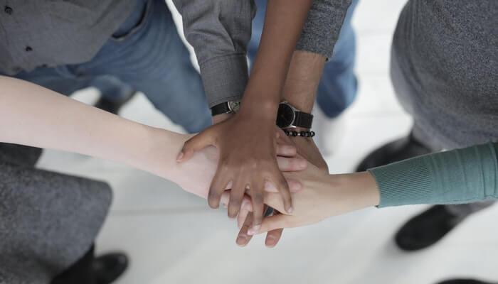 Mãos de cinco pessoas unidas representando a integração dos canais no omnichannel