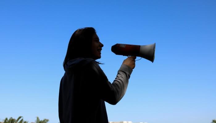 Mulher com megafone, representando o outbound marketing. Ao fundo, vemos um céu muito azul