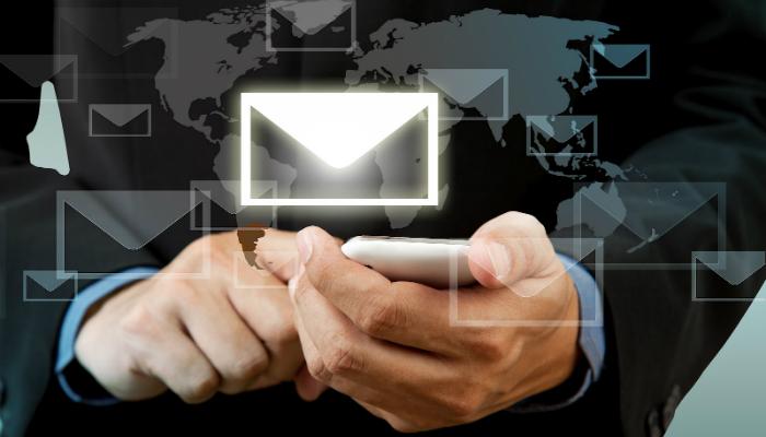 Mãos de homem mexendo em smartphone com ilustração de envelope acima, representando o poder do e-mail marketing