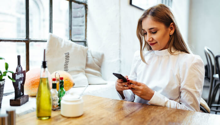 Mulher com blusa branca estilosa sentada à mesa, mexendo no celular, representando as redes sociais para ecommerce de moda