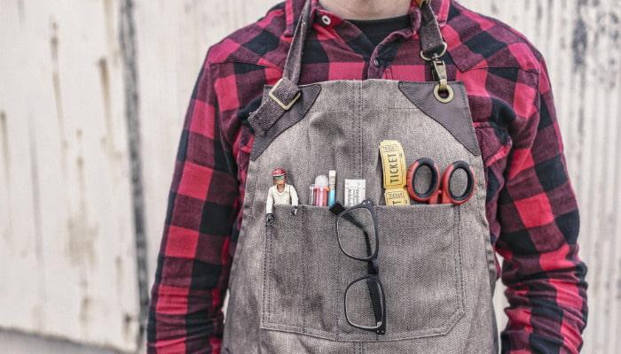 Homem com utilidades em bolso de avental representa soluções inovadoras para e-commerce