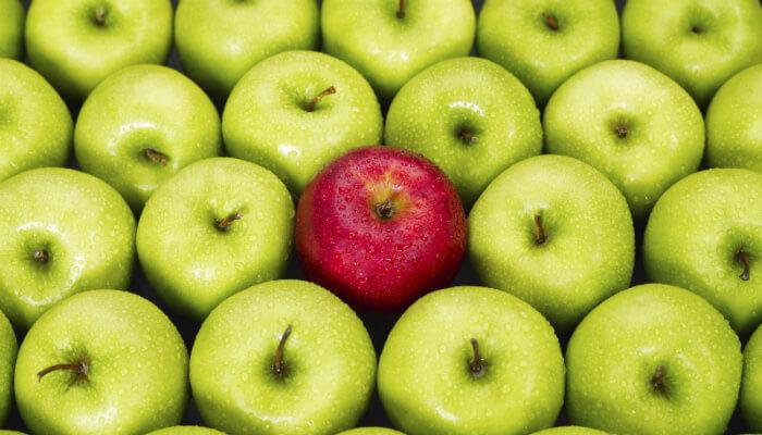 Foto de maçãs verdes, com apenas uma vermelha no meio, representando o teste A/B para email marketing