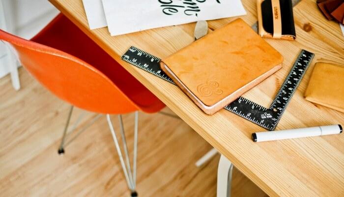 Escrivaninha com caderno e régua em evidência, representando a URL parametrizada