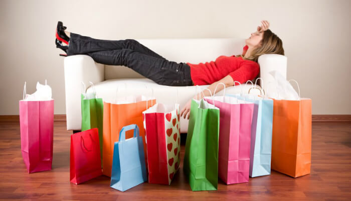 Mulher deitada em sofá com sacolas sacolas de compra em volta