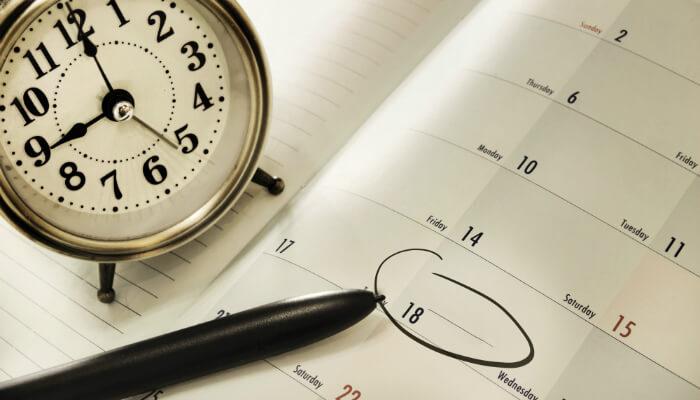 Relógio sobre agenda, representando como agendar posts pelo Hootsuite