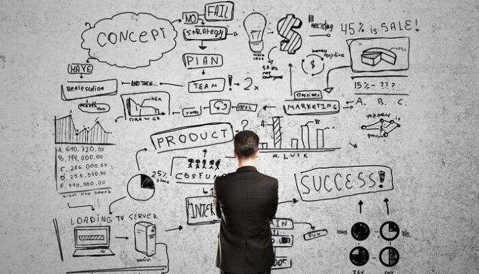 Homem de terno de costas olha para painel com informações para a análise de mercado
