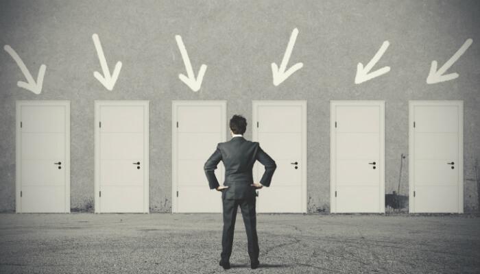 Homem parado em frente a seis portas, representando a análise de tendência