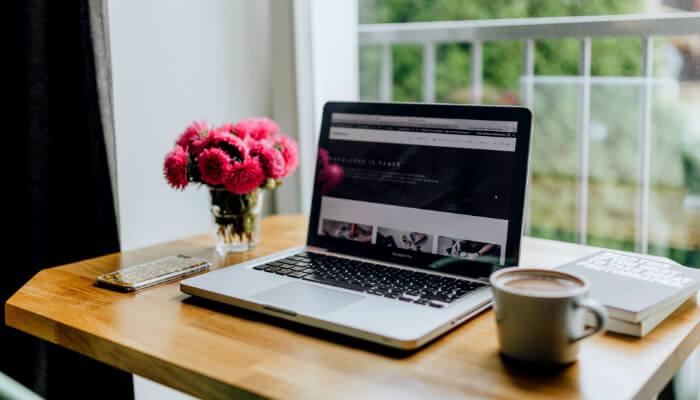 Mesa com computador e vaso de flores, representando o e-mail marketing do dia das mães