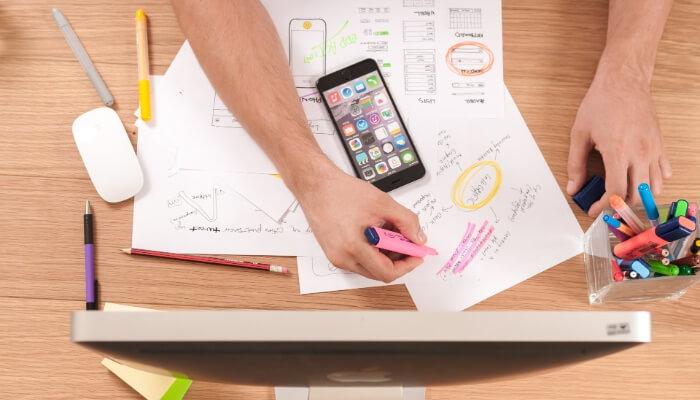 Mãos escrevem sobre mesa cheia de papéis e representam como emitir notas fiscais eletrônicas