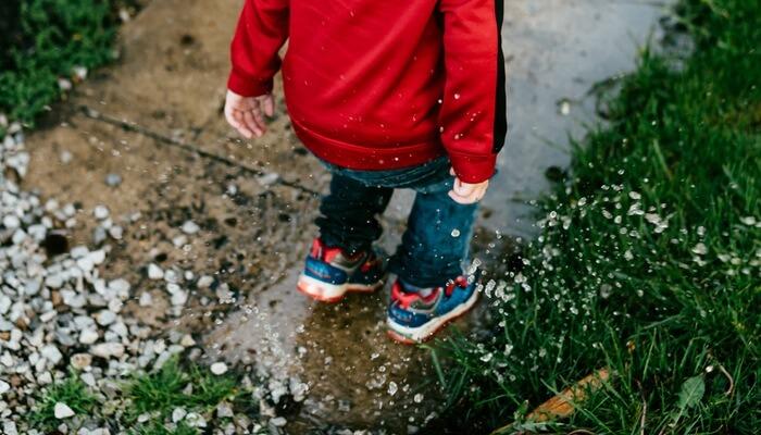 Criança pulando em poça d'água
