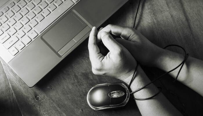 Mãos amarradas com fio de mouse de computador, representando as fraudes virtuais