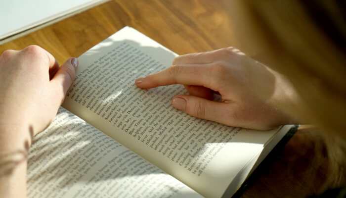 Mulher lê livro glossário com termos da administração
