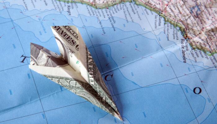 Avião feito com dobradura de cédula sobre mapa representa o Google Adsense