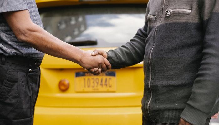 Imagem mostrando duas pessoas se cumprimentando com um aperto de mãos.