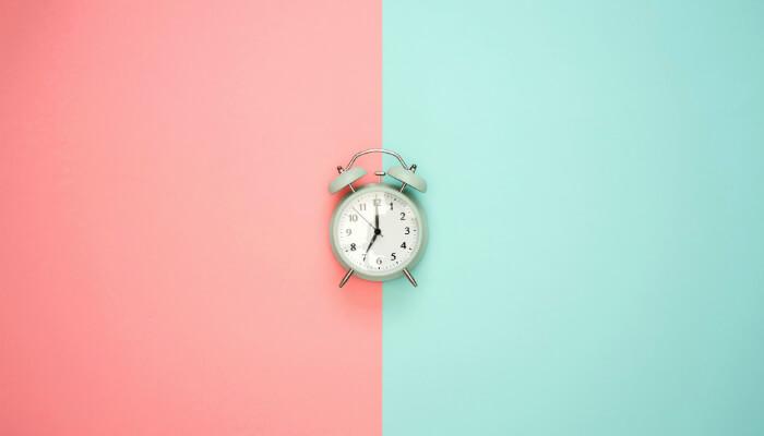 Relógio sobre fundo metade rosa, metade azul, representando os melhores horários para postar no Instagram