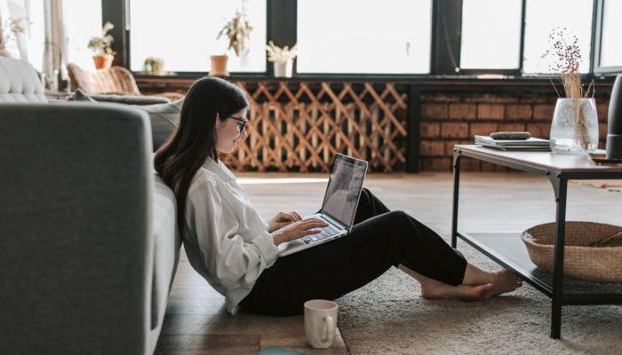 Mujer sentada en el piso con laptop
