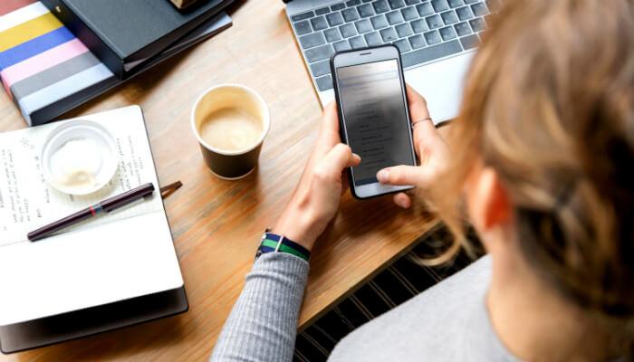 Pessoa mexe em celular, representando a relação entre mobile e vendas
