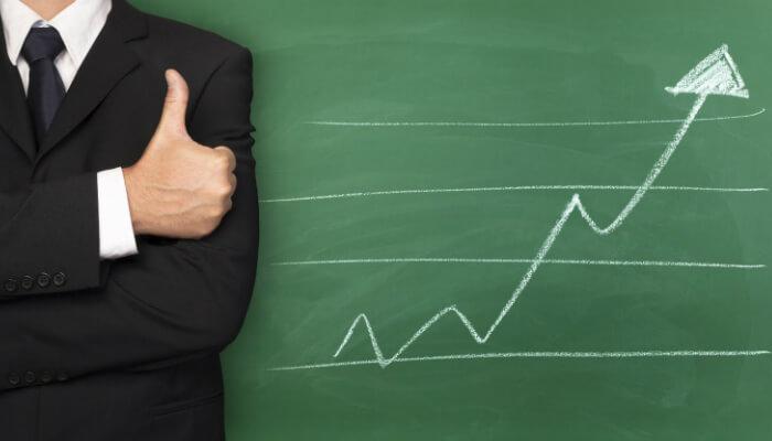 Homem faz sinal de positivo em frente a lousa com desenho de gráfico crescente, representando os relatórios do Google Ads