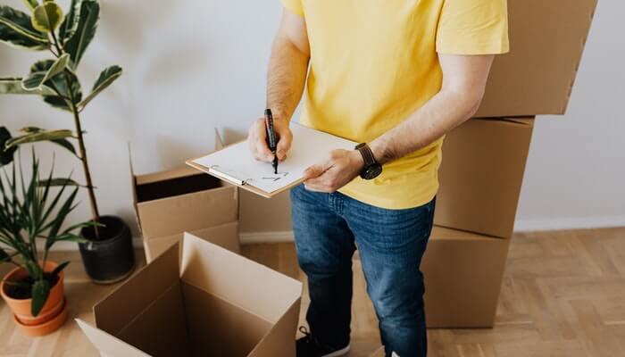 Homem de camisa amarela em frente a caixa escreve em uma prancheta, representando os tipos de envio dos Correios