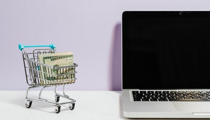 Imagem mostrando um computador ao lado de uma miniatura de um carrinho de compras, simbolizando o e-commerce.