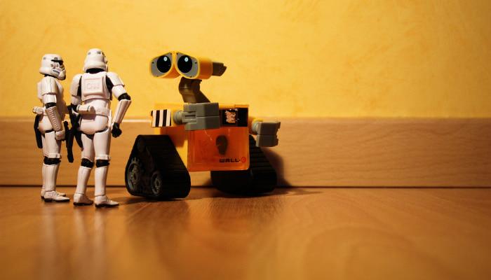 Robô de brinquedo Wall-E em frente a bonecos de Stormtroopers, da saga Star Wars
