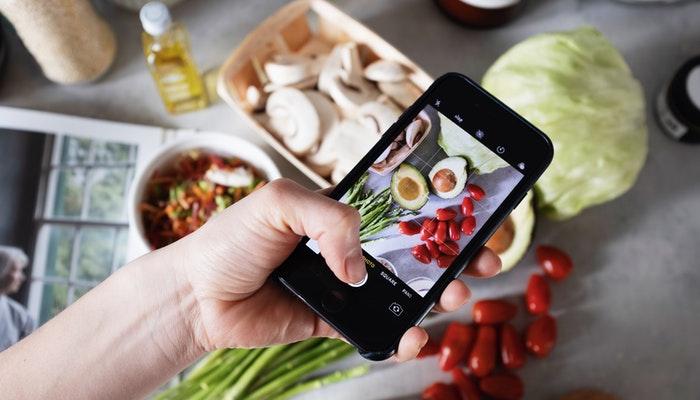 Imagem mostrando uma pessoa tirando fotos de alimentos com um celular.