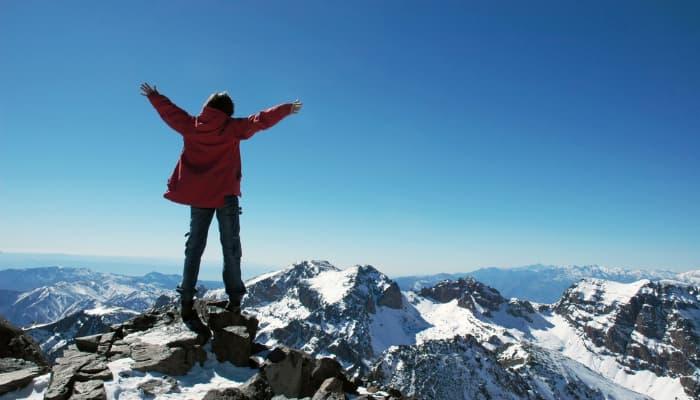 Imagem mostrando uma pessoa no topo de uma montanha.