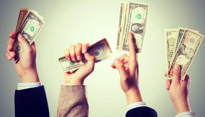 Mãos segurando cédulas representam como definir uma estratégia de preços