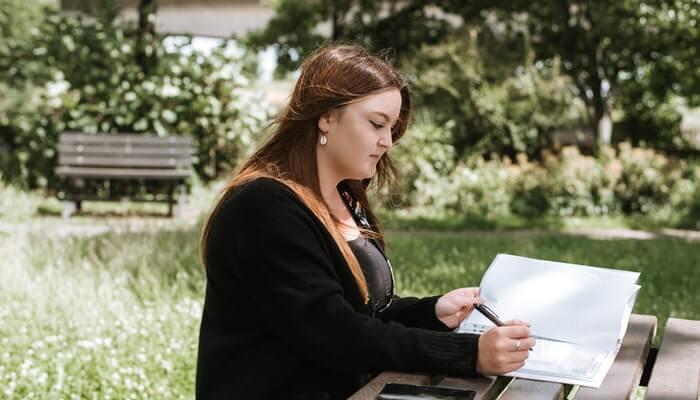 Mulher escreve em caderno, como se estivesse revisando dados de usuários para se adequar à LGPD