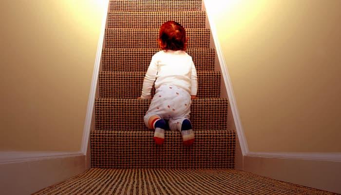 Imagem mostrando um bebê engatinhando sobre uma escada.