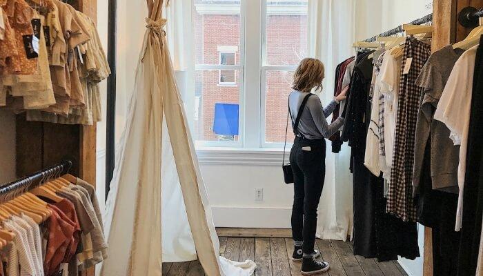 Mulher mexe em roupas em loja, representando a buyer persona