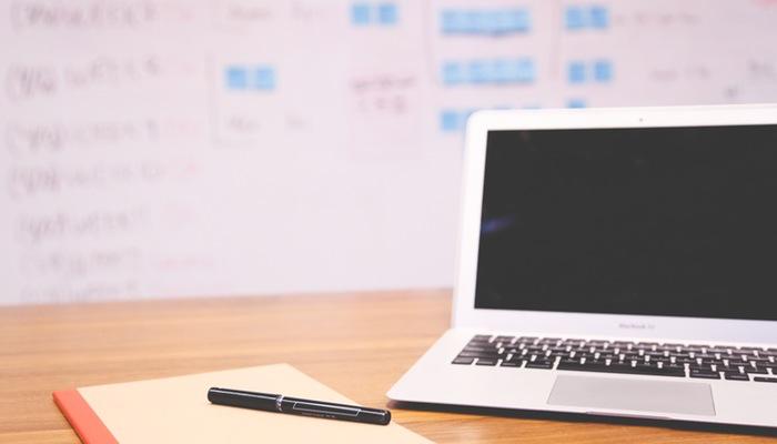 Computador com caderno e caneta em uma mesa, com lousa cheia de cálculos e post-its no fundo, representando como calcular o markup