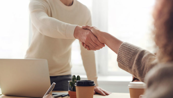 Como conseguir inversionistas un hombre y una mujer dándose un apretón de manos en una oficina