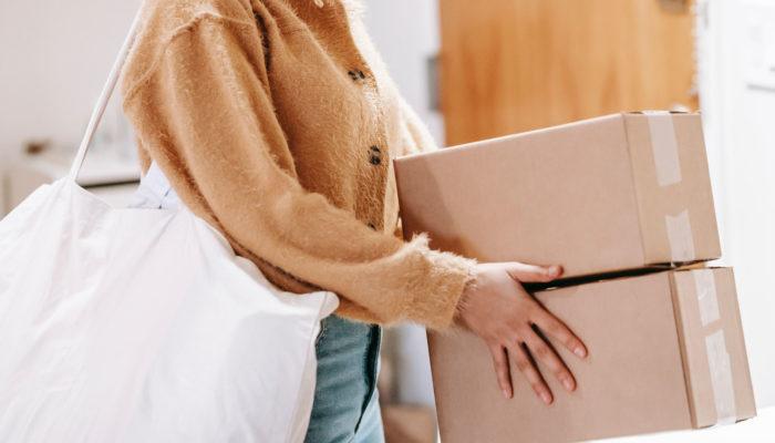 Mujer con una bolsa grande al hombro y dos cajas de cartón en las manos