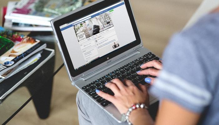 Imagem mostra mulher acessando computador, o meio como vender pelo Facebook