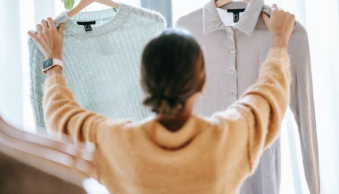 Imagem mostrando uma mulher segurando duas peças de roupa.