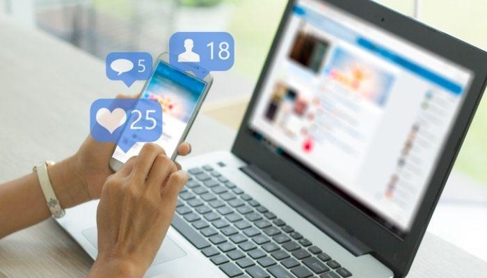Foto de mãos mexendo em smartphone no Facebook, com um notebook aberto ao fundo, representando como integrar loja virtual com o Facebook