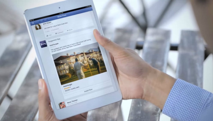 Mãos de homem seguram um tablet aberto no feed do Facebook